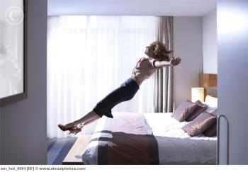Woman jumping onto bed
